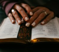 An image of a woman's hands resting on her Bible to represent the Thursday night Bible Study in Gold Canyon. Bible Study in Gold Canyon